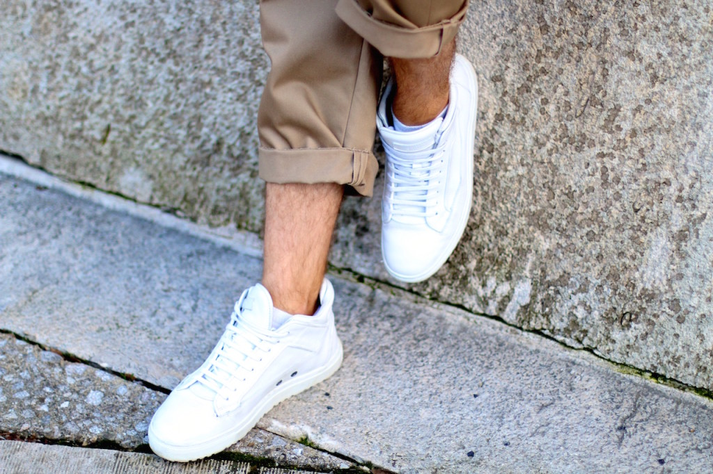 stylisch young men stands in front of concrete wall wearing H&M Studio SS16 Collection wide rolled up slacks in sandy beige tones with white sneakers a progressive spring outfit for the creative modern man spring/summer trends 2016