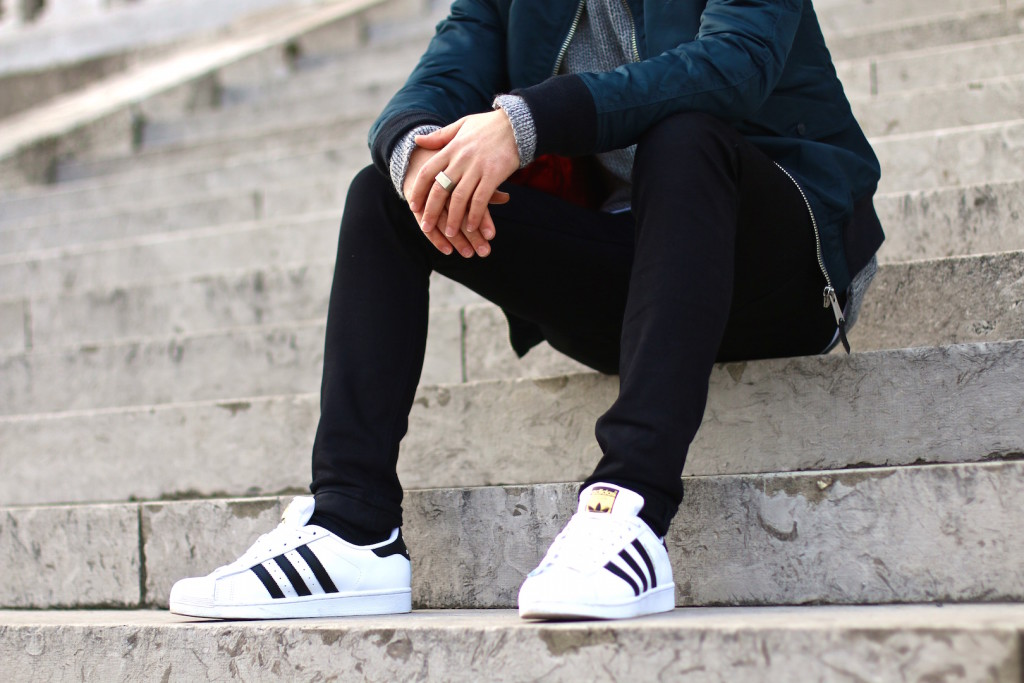 Maleblogger Sitting on Stairs wearing Spring Outfit featuring Adidas Superstars and Schott NYC Bomber Jacket and BLKDNM jeans