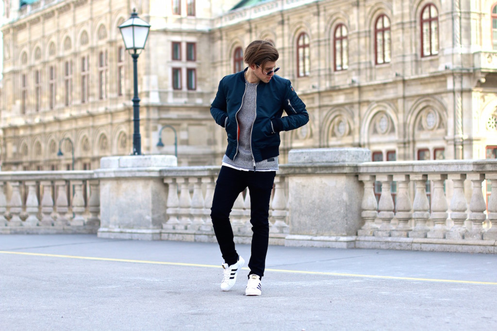 Menswear Blogger Meanwhileinawesometown wearing bomber jacket jeans and sweater by about you in front of Opera House of Vienna