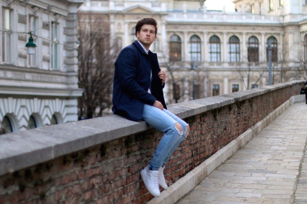 Menswear Blogger sitting on wall wearing ripped jeans by Neuw Denim and navy Wintercoat by Selected Homme