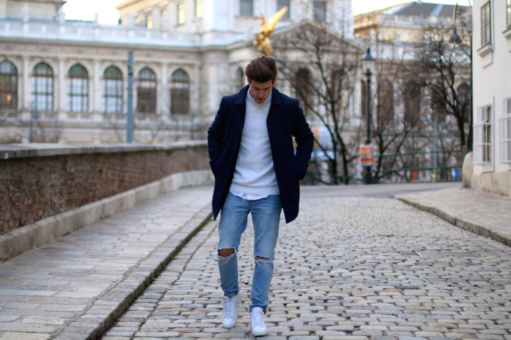 Menswear blogger showing outfit of the day featuring a blue winter coat by Selected homme ripped jeans by Neuw and ETQ sneakers 1