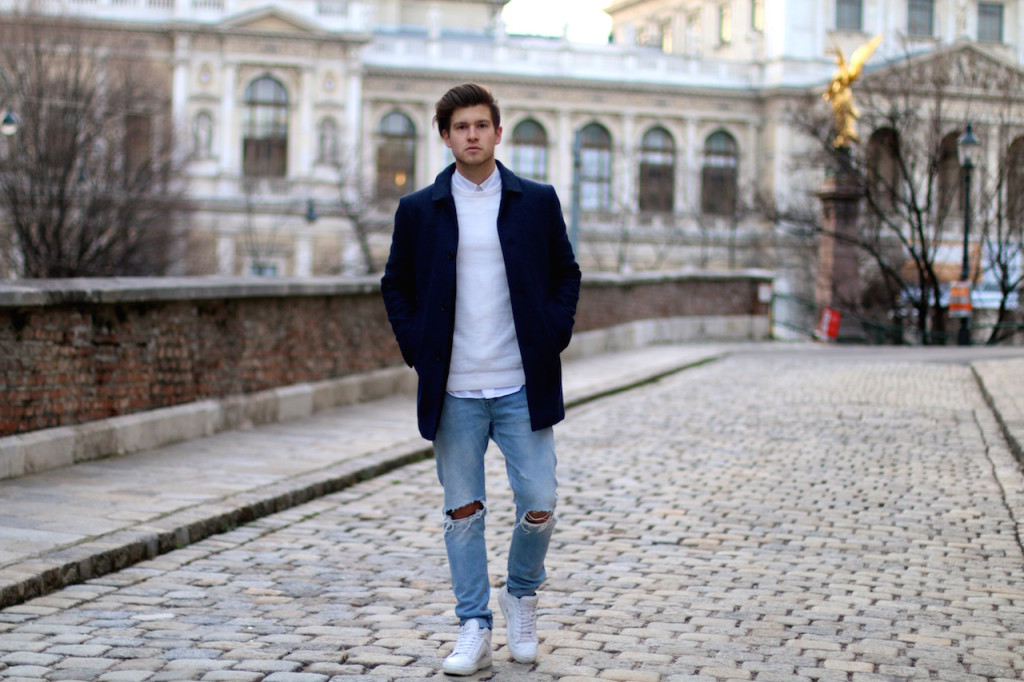 Menswear blogger showing outfit of the day featuring a blue winter coat by Selected homme ripped jeans by Neuw and ETQ sneakers