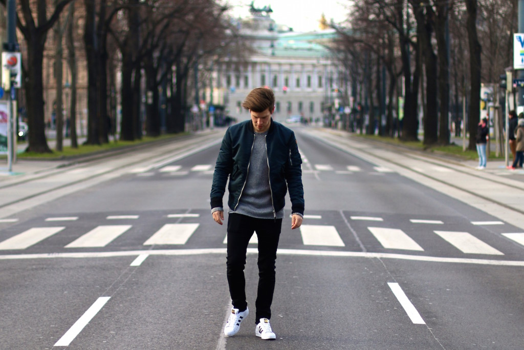 Menswear blogger wearing bomber jacket black jeans and grey sweater by aboutyoude on viennese Ring street