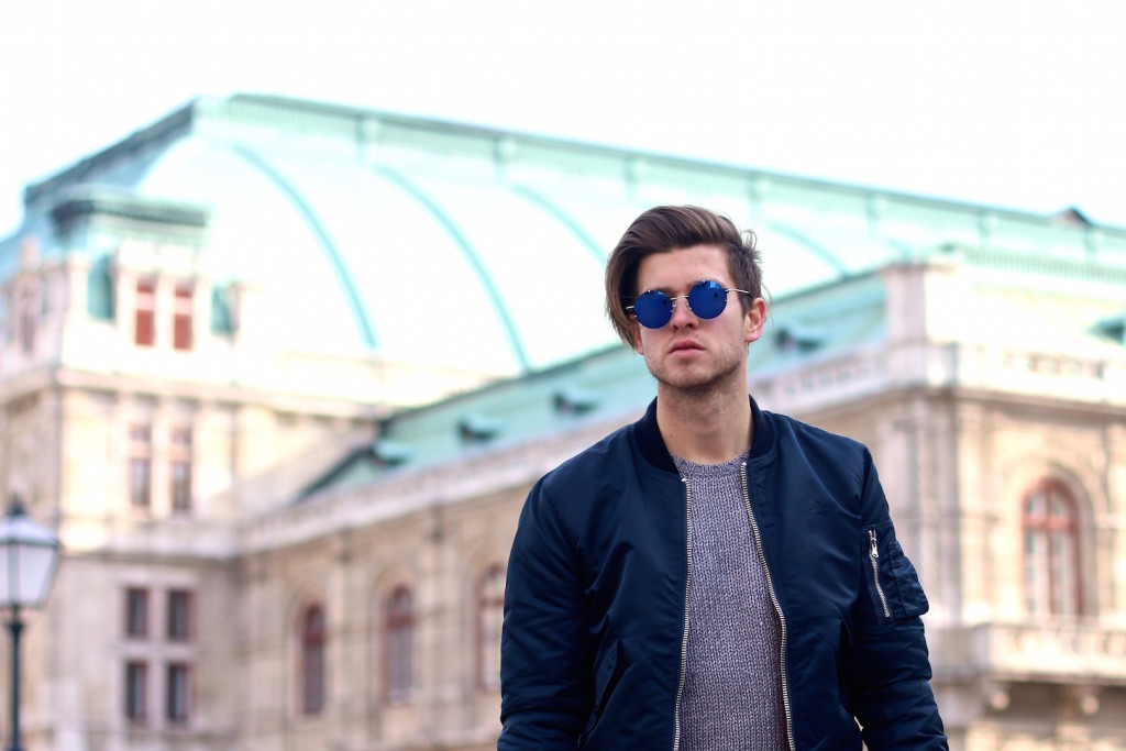 Portrait of Maleblogger in front of Vienna Opera House wearing blue bomber jacket by Schott NYC and sunglasses by Spitfire