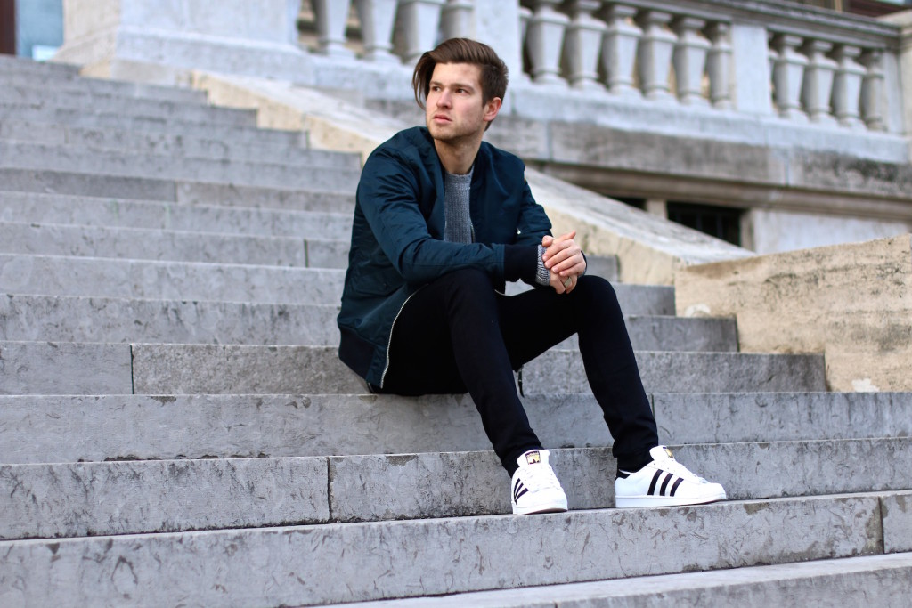 male blogger sitting on stairs wearing blue bomber jacket and black jeans from aboutyoude